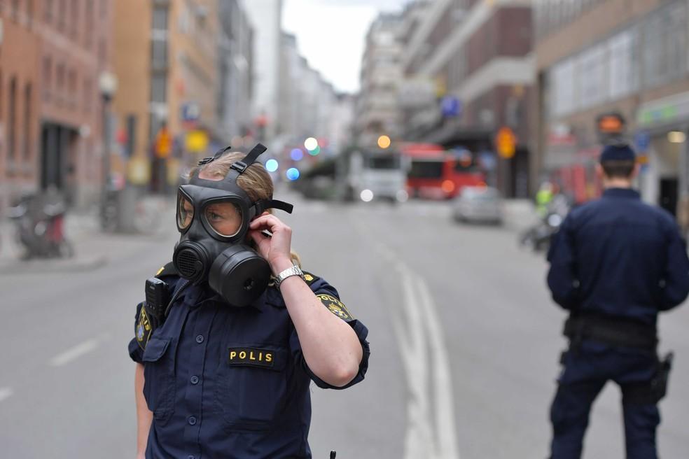 Policial usa mascara após caminhão colidir contra loja em Estocolmo, na Suécia, nesta sexta-feira (7)  (Foto: Jessica Gow, TT News Agency via AP)