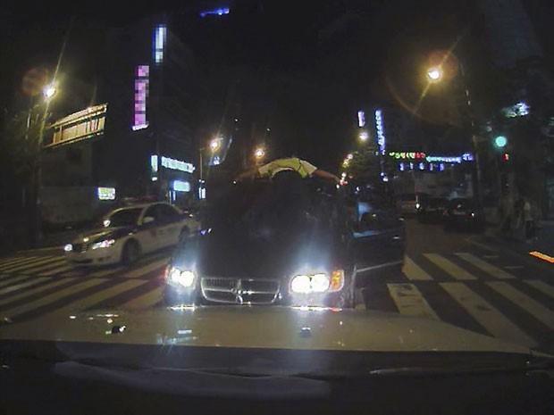 Em setembro deste ano, o agente de trânsito sul-coreano Kim Hyun-cheol saltou sobre um carro para prender um suspeito de tráfico de drogas em Busan, na Coreia do Sul. O policial se segurou por 25 minutos sobre o capô do veículo. Graças à sua ação, o agente recebeu uma promoção. (Foto:  Busan Police Agency/AP)