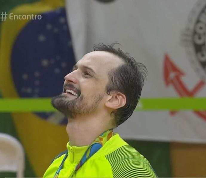 Lipe vendo a bandeira do Brasil subir após ganhar medalha de ouro (Foto: TV Globo)