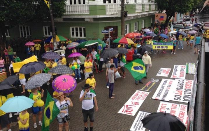 Sob chuva, manifestantes se reúnem no Centro de Manaus