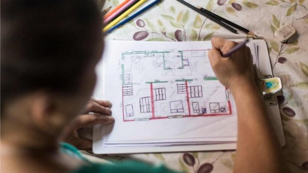 Flávia Fonseca dos Santos, participante da segunda edição do projeto, com planta da casa que ela mesma desenhou (Foto: Bruno Figueiredo/BBC)