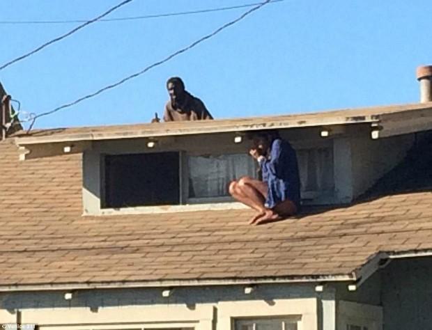 Foto assustadora mostra momento em que mulher se esconde no telhado de casa para fugir de invasor