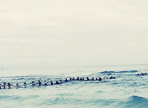 Corrente humana formada por banhistas tentando alcançar família que se afogava (Foto: Facebook)