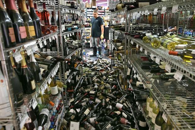 Funcionário observa as dezenas de vinhos que foram derrubados das prateleiras de uma loja em Napa após o terremoto (Foto: Justin Sullivan/Getty Images/AFP)