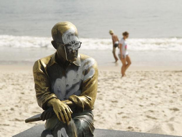 A estátua do poeta Carlos Drummond de Andrade, que fica na Praia de Copacabana, na Zona Sul do Rio, foi pichada na noite desta quarta-feira (25). O monumento já tinha sido alvo de outros atos de vandalismo. (Foto: Marcelo Carnaval/Agência O Globo)