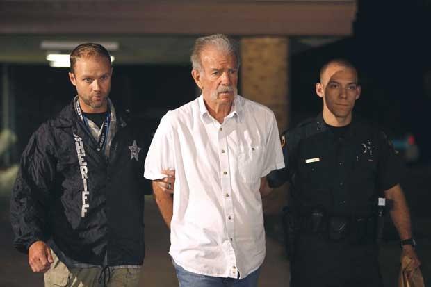 Pastor Terry Jones é escoltado por policiais após ser detido na Flórida na quarta-feira (11) (Foto: Lakeland Ledger, Michael Wilson/ AP)