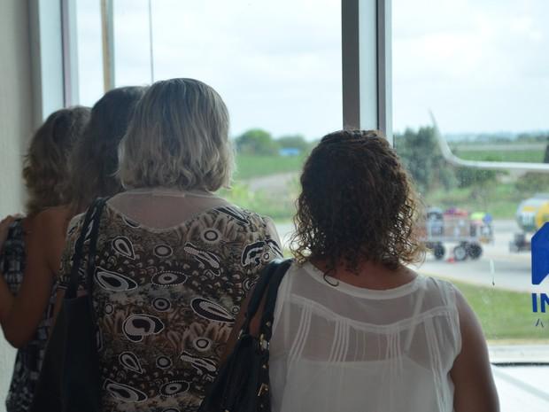 Mãe e irmãs de Marcos Nogueira observam a chegada das urnas no Aeroporto de João Pessoa (Foto: Dani Fechine/G1)
