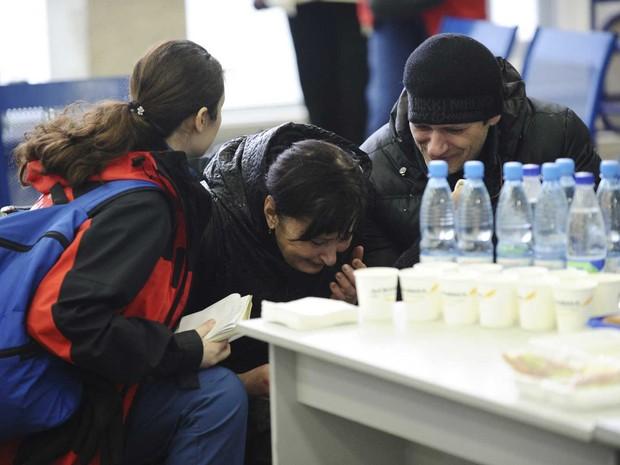 Psicólogo do Ministério das Emergências russo consola familiar de vítima (Foto: Sergey Pivovarov / Reuters)