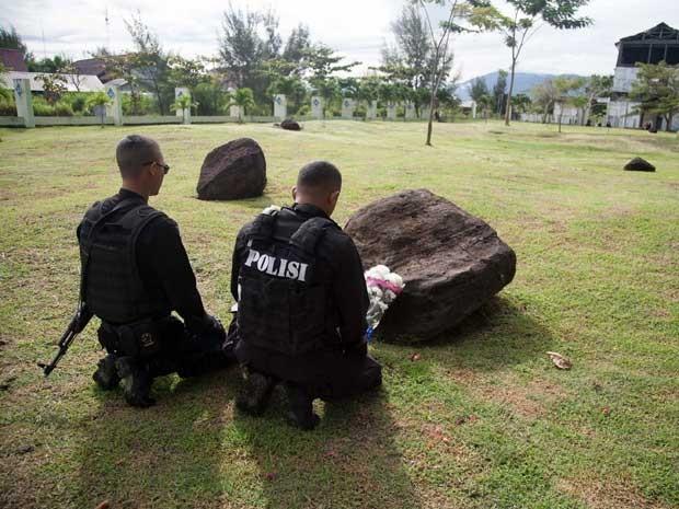 Policiais rezam por seus amigos e parentes mortos em uma vala comum para as vítimas do grande tsunami de 2004. (Foto: Chaideer Mahyuddin / AFP Photo)