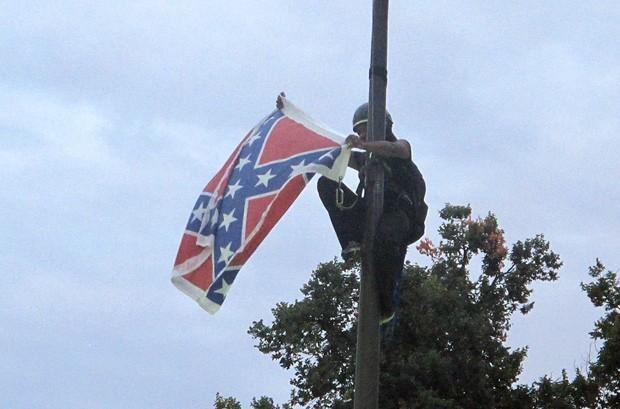 Ativista escalou nove metros de altura para retirar a bandeira  (Foto: AP Photo/Bruce Smith)