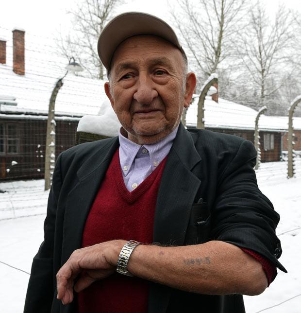 O sobrevivente Sam Beller mostra o seu número de prisioneiro tatuado no braço enquanto visita Auschwitz nesta segunda-feira (26) (Foto: JANEK SKARZYNSKI / AFP)