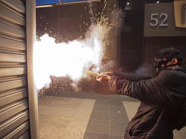 Rio de Janeiro - Manifestante atira rojão na direção de policiais no Centro do Rio (Foto: Nicolas Tanner/AP Photo)