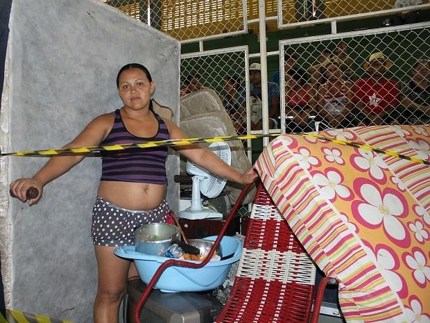 Dona de casa guardando os pertences que os vizinhos conseguiram resgatar (Foto: Girlene Medeiros / G1 AM)