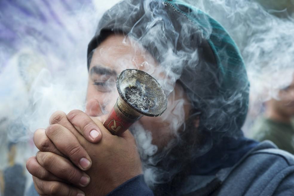 Homem fuma maconha durante protesto na Cidade do Cabo, África do Sul (Foto: RODGER BOSCH/AFP)