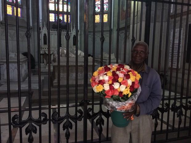 Seu João foi visitar o túmulo na véspera, mas só fará a entrega das rosas depois de abençoadas na missa (Foto: Bruno Rodrigues/G1)