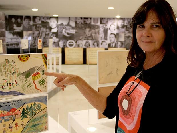 Karen Zolko, uma das curadoras da mostra, ao lado de desenhos (Foto: Vianey Bentes/TV Globo)