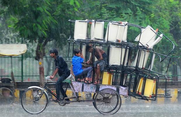 Condutor de riquixá equilibra cadeiras sob a chuva na Índia nesta segunda-feira (24) (Foto: Sanjay Kanojia/AFP)