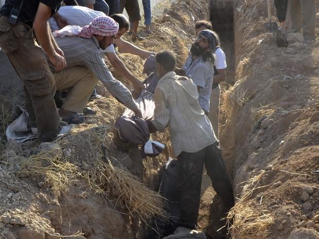 Homens enterram corpos de mortos em ataques na Síria em valas no subúrbio de Damasco. (Foto: Bassam Khabieh/Reuters)