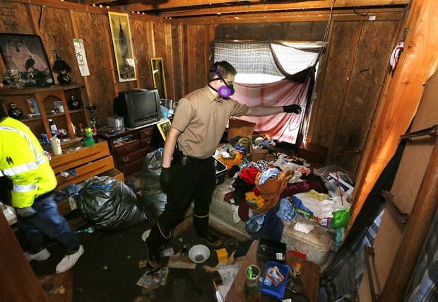 Policial inspeciona casa imunda na qual três crianças foram encontradas abandonadas em Lake Stevens, no estado de Washington, nos EUA (Foto: The Herald, Mark Mulligan/AP)
