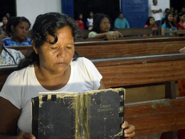 Indígena Zila Santos lendo a bíblia durante o culto na aldeia Kumenê (Foto: Abinoan Santiago/G1)