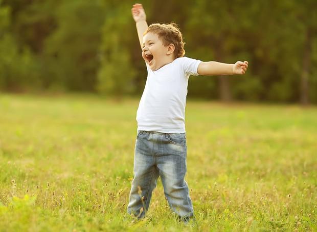 Criança feliz sorrindo e levantando os braços (Foto: Shutterstock)