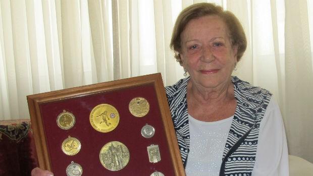 Dona Laura exibe quadro de medalhas de Araken Patusca - Santos (Foto: Gustavo Serbonchini / globoesporte.com)