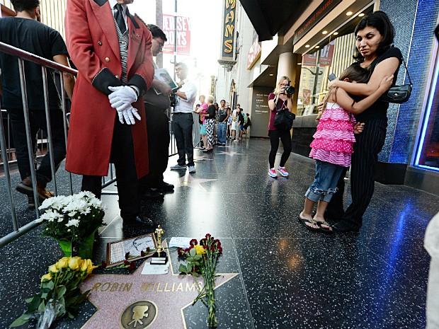 Fãs observam a estrela do ator Robin Williams na Calçada da Fama, horas depois da morte do comediante nesta segunda-feira (Foto: Robyn Beck/APF Photo)