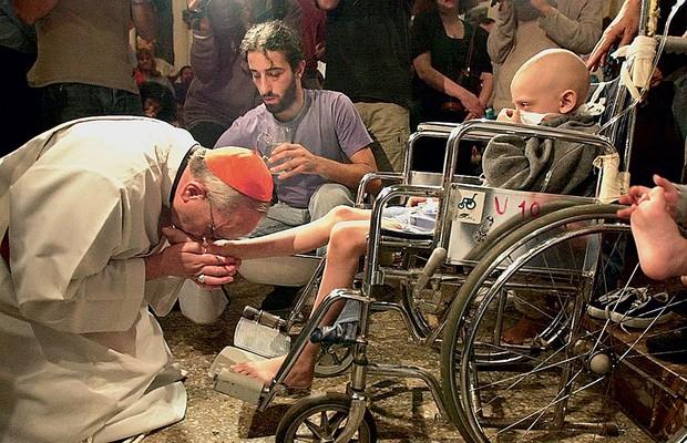 """POR QUE, DEUS? Bergoglio, então cardeal em Buenos Aires, beija os pés de uma criança com aids, em 2001. Ele diz que uma pergunta, feita por Dostoiévski, ronda seu coração:  """"Por que as crianças sofrem?"""" (Foto: AFP)"""