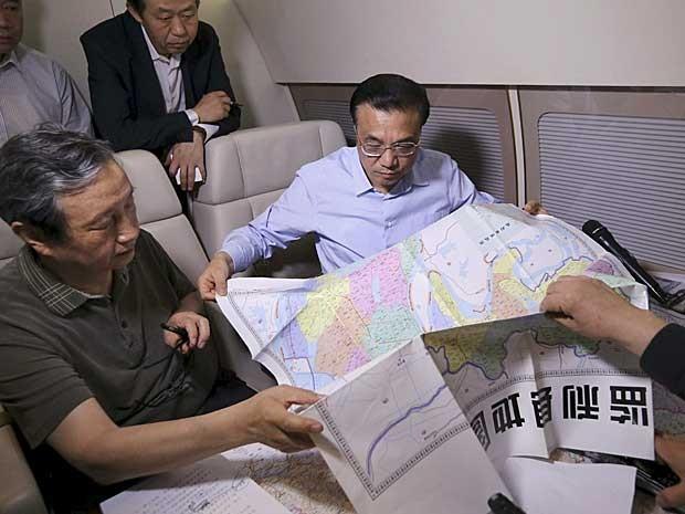 Premiê chinês, Li Keqiang, discute plano de resgate com um mapa nas mãos (Foto: Reuters)