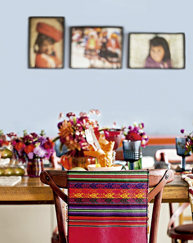 Tapeçaria peruana na cadeira e fotos de crianças de Cuzco na parede do apartamento de Marisabel (Foto: Elisa Correa/Editora Globo)