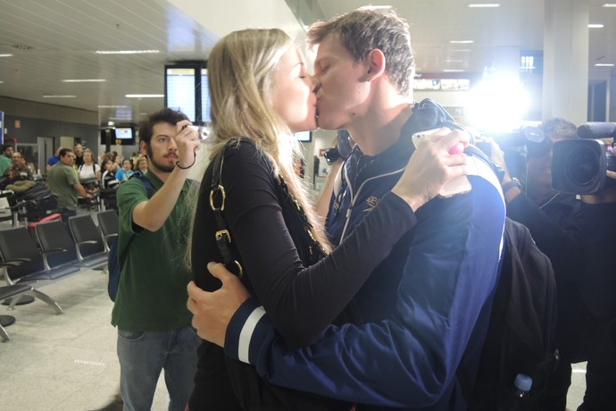Cesar Cielo beija a esposa Kelly ao desembarcar em São Paulo (Foto: David Abramvezt)