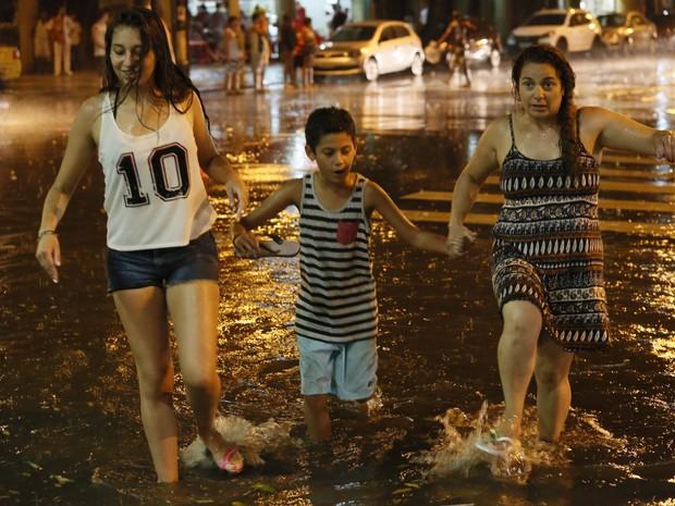 Moradores caminham em rua alagada no Centro do Rio de Janeiro na noite deste domingo (Foto: Marcos Tristão/Agência O Globo)