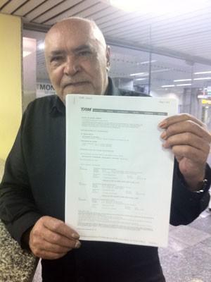 Adauto mostra a passagem de avião: embarque previsto para a noite desta terça (Foto: Isabela Marinho/G1)