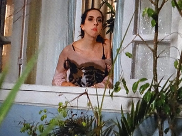 Frô vê tudo pela janela e se morde de ciúmes (Foto: Guerra dos Sexos / TV Globo)