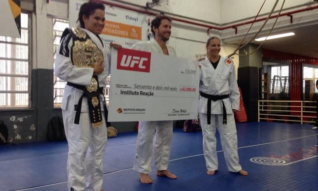 Flavio Canto sorridente ao receber ao lado de Amanda Nunes cheque de 62 mil reais