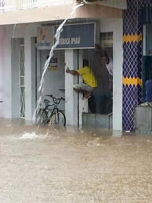 Homem tenta escapar de alagamento e fica 'agarrado' em parede de Lotérica (Foto: Portal de Notícias Giro em Ipiaú)