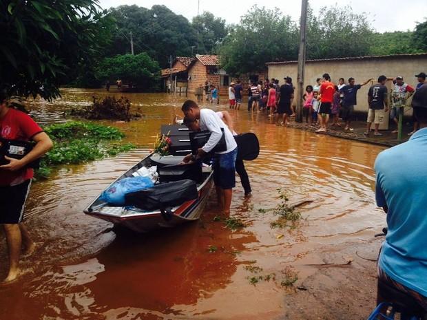 Moradores tentam salvar móveis, roupas e eletrodomésticos usando barcos (Foto: Alexandre Alves/TV Anhanguera)
