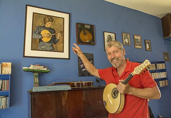 O músico Pedro Amorim aponta para uma pintura realizada por sua mãe há 40 anos na qual ele já aparece com um bandolim  (Foto: © Haroldo Castro/Época)