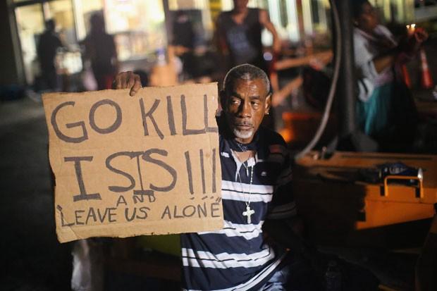 Manifestante em Fergunson pede em cartaz: 'Vão matar o ISIS [Estado Islâmico] e nos deixem em paz' durante protesto contra a morte de um jovem negro por um policial (Foto: Scott Olson / Getty Images North America / AFP)