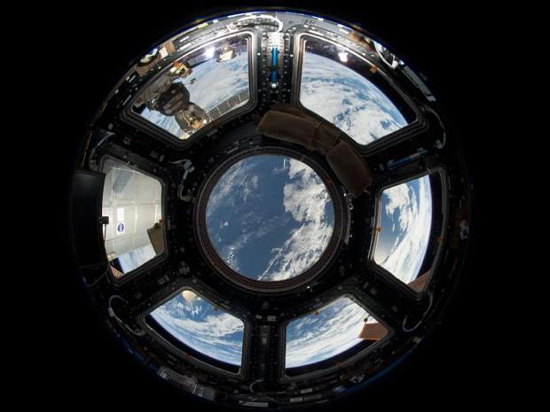 A Nasa divulgou nesta segunda-feira (17) a visão do planeta Terra visto da cúpula do lado terrestre, voltado à Estação Espacial Internacional. No primeiro plano superior esquerdo, é possivel ver uma cápsula da tripulação russa Soyuz. Já no canto inferior direito, um painel solar pode ser visto. (Foto: Nasa)