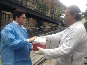 No simulado na Fiocruz, médico entrega coleta de sangue para análise no Instituto Evandro Chagas, no Pará (Foto: Guilherme Brito / G1)