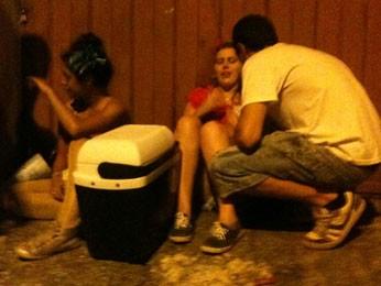 Mulheres sentadas na calçada após confusão no carnaval do bairro Santa Tereza. (Foto: Renan Ramalho/G1)