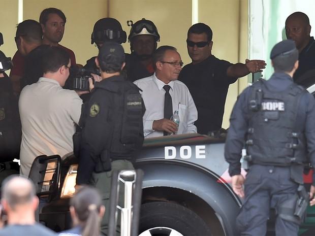 O funcionário do hotel que foi feito refém durante sete horas e meia deixa o local. Segundo a polícia, ele estava tranquilo e disse que não sofreu agressão (Foto: Evaristo Sa/AFP)