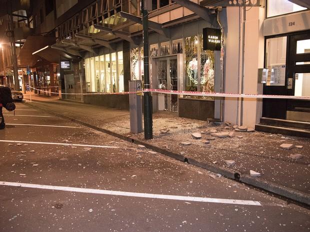 Escombros de concreto caídos de edifícios são vistos em uma calçada em Wellington depois do terremoto (Foto: Marty Melville / AFP)