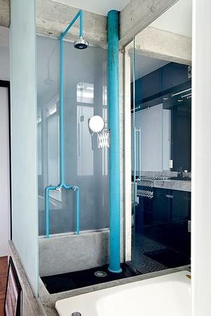 Na área do chuveiro deste banheiro, a tubulação e o cano de esgoto foram pintados de azul. O tom vibrante ganha ainda mais força na presença da estrutura de concreto. Projeto do arquiteto Diogo Oliva (Foto: Victor Affaro/Casa e Jardim)