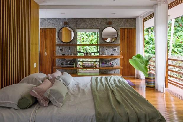 Dois espelhos com formato que lembram escotilhas de barco foram instalados na parede de pedras entre o banheiro e o quarto da casa de praia da arquiteta Fabiana Avanzi (Foto: Edu Castello / Editora Globo)