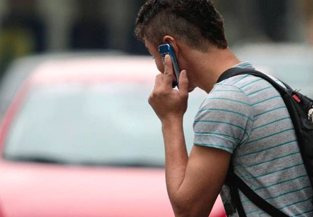 Jovem usa celular ao atravessar a rua no Rio de Janeiro (Foto: Agência O Globo)