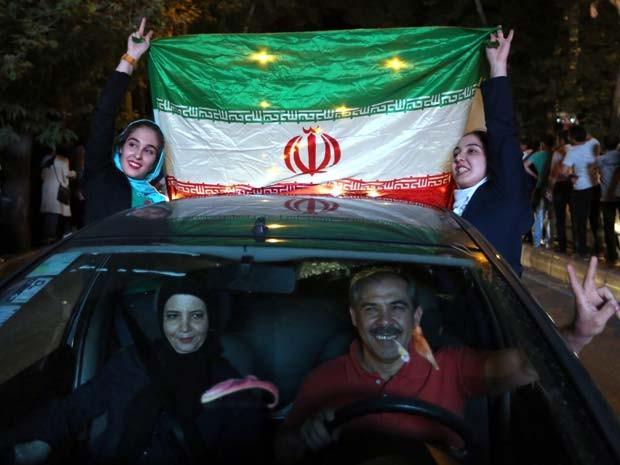 Iranianos saem às ruas de Teerã nesta terça-feira (14) para comemorar o acordo que limita a capacidade nuclear do país (Foto: AFP PHOTO / ATTA KENARE)