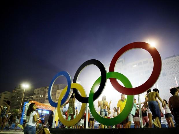 Cariocas e visitantesposam para foto nos anéis olímpicos instalados na praia de Copacabana; nesta região há provas de ciclismo de rua, vôlei, maratona aquática e triatlo  (Foto: AP Photo/David Goldman)