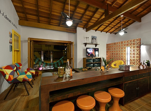 Bancada de madeira tem bancos virados para a sala de TV. Integração total no espaço! (Foto: Vanessa Bohn/Bohn Fotografias)